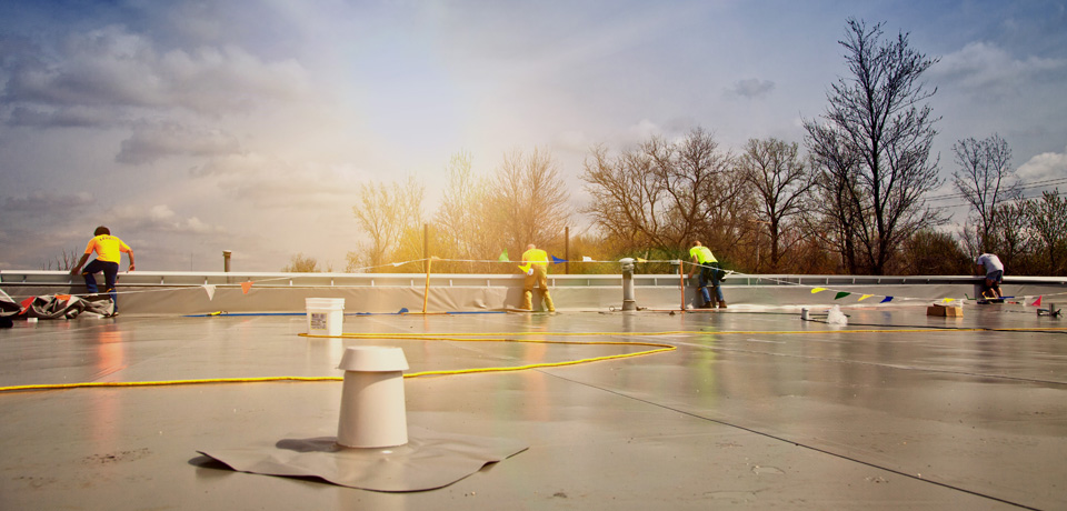 commercial roofing contractors working on a flat roof