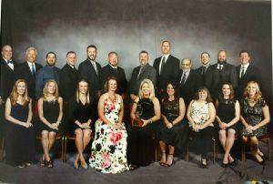formal portrait of Damschroder Roofing Team with award